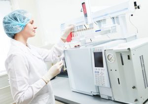 Lab Technician using a Machine